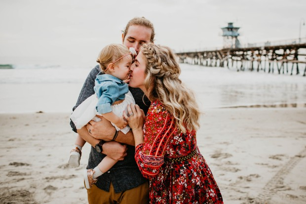 mom nuzzling baby at beach