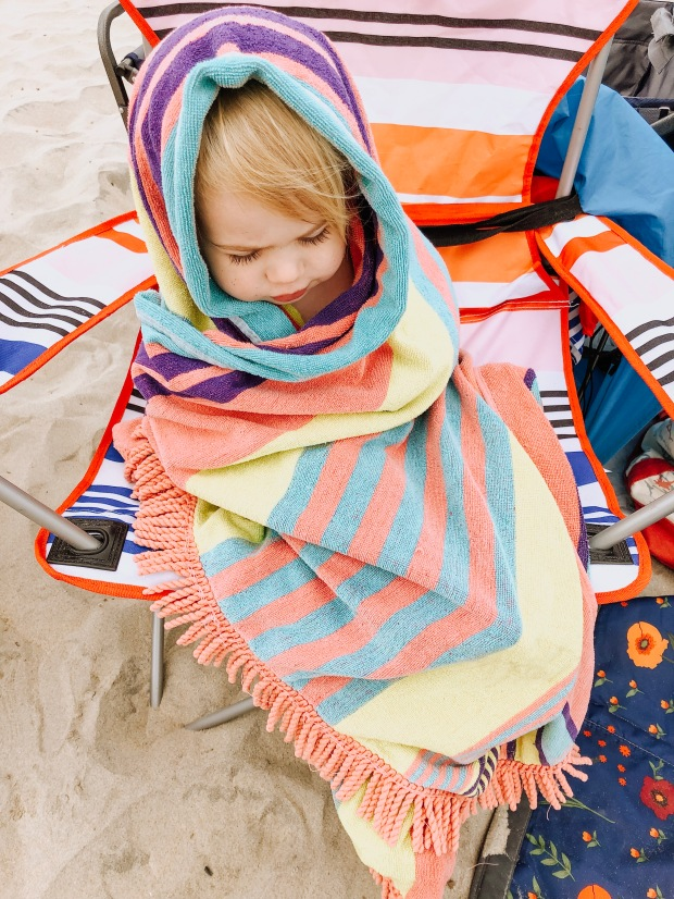 toddler girl on beach in a towel